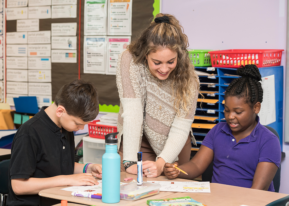 Smiling teacher helps two students with an assignment
