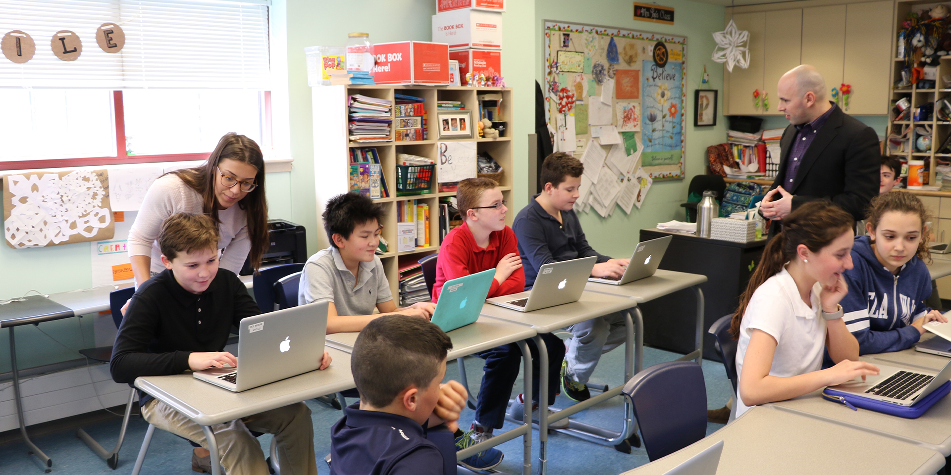 Two teachers help students with laptops in classroom