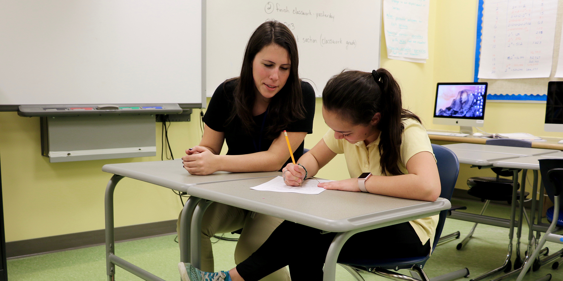 Teacher helps student with a writing assignment
