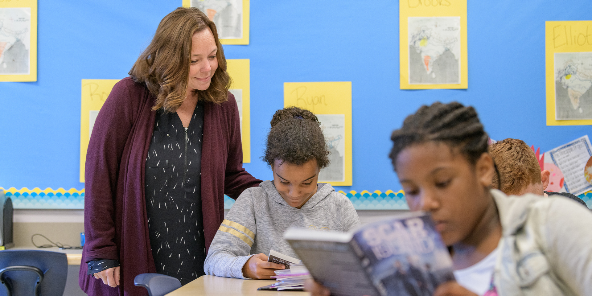 Teacher looks over student's shoulder as she reads book